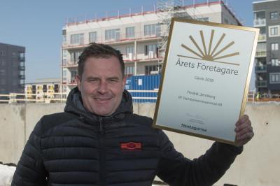 Fredrik visar upp diplomet, i bakgrunden ett av husen han bygger på Gävle Strand