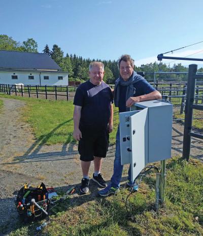 Ricky Andersson och Nicolas Dimitri poserar glatt med manöverskåpet som styr skrittmaskinen.