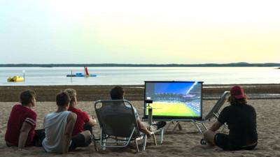 Världens smartaste mobila multimediaprojektor projicerar på stranden.